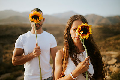 Woman and man hiding face with sunflowers during sunset - p300m2206981 by Miguel Frias