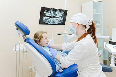 Female dentist putting dental drape on little girl sitting in dentists chair - p300m2265155 by Ekaterina Yakunina