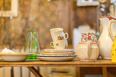 Decorative dishes piled on table - p429m767867 by dotdotred