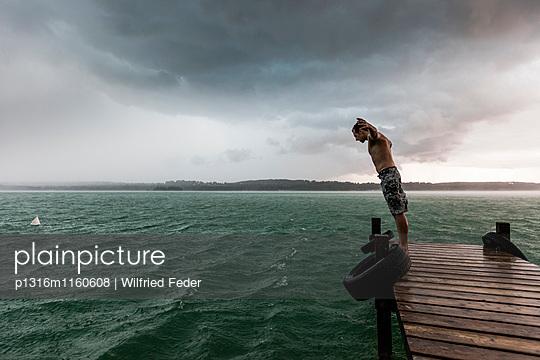 Junger Mann lehnt sich auf einem Steg in den Wind, Starnberger See, Bayern, Deutschland - p1316m1160608 von Wilfried Feder