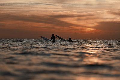 Surfers in ocean at sunset - p1166m2137246 by Cavan Images