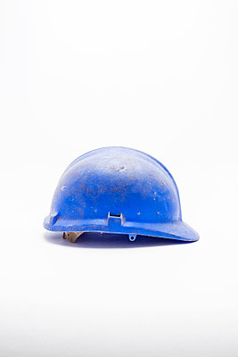 A worn, scratched and dirty blue hard hat or safety helmet on a white background - p1302m2126949 by Richard Nixon