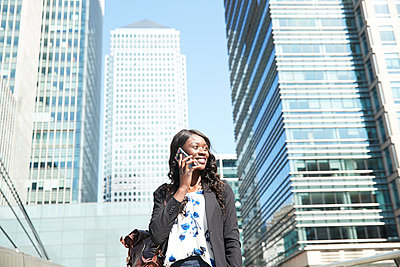 Businesswoman looking away while talking on mobile phone standing in city - p300m2241103 by Pete Muller