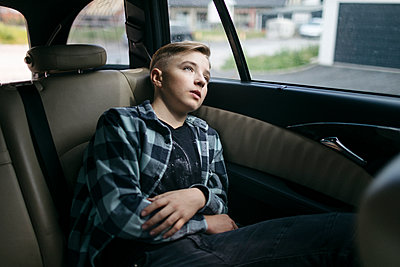 Thoughtful boy looking through window while sitting in back seat of car - p300m2256113 by Katharina Mikhrin