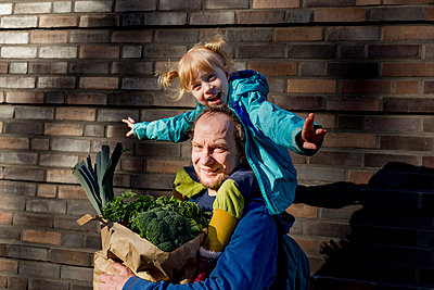 Smiling man carrying cheerful daughter while holding bag of vegetables at wall - p300m2277111 by Irina Heß