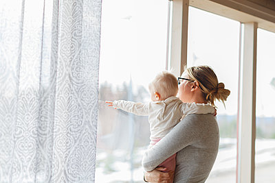Mother and  baby beside window in Sweden - p352m1536507 by Christian Ferm