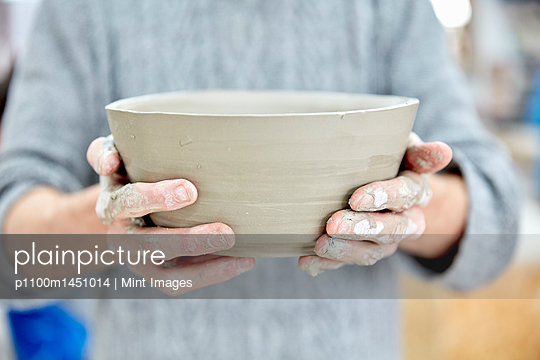 A person holding a freshly thrown clay pot with gently sloping sides.