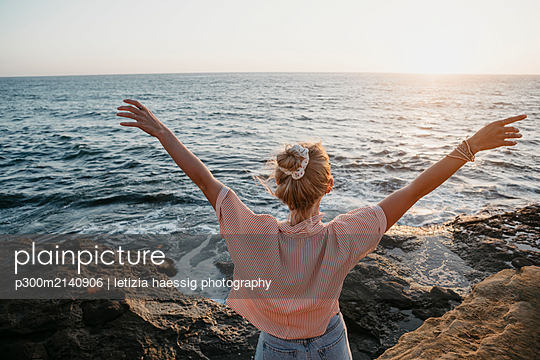 Rear view of young woman at the sea with raised arms, Sunset Cliffs, San Diego, California, USA - p300m2140906 by letizia haessig photography