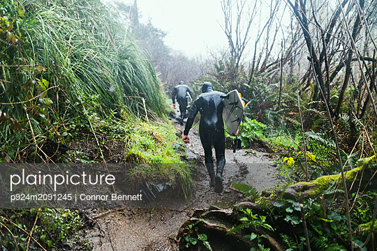 Young male surfers in wetsuits walking up coastal dirt track in rain, Arcata, California, United States - p924m2091245 by Connor Bennett