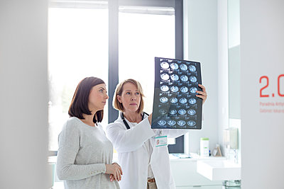 Serious doctor and patient reviewing x-rays in examination room - p1023m1086286f by Agnieszka Wozniak