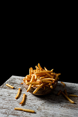French fries in a earthenware bowl, on a table - p1423m2152551 by JUAN MOYANO