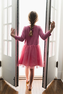 Rear view of girl (6-7) walking through doorway into light - p1427m2174022 by Jamie Grill