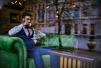 Fashionable young man sitting on couch in a cafe drinking coffee - p300m1549508 by Zeljko Dangubic