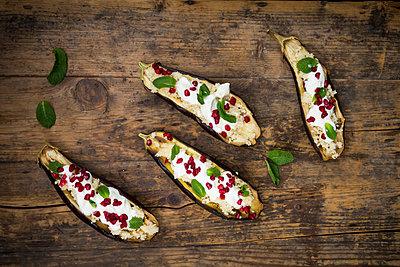 Filled aubergine, couscous, yogurt sauce, mint and pomegranate seeds - p300m1549793 by Larissa Veronesi