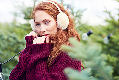 Portrait of redheaded young woman with freckles wearing ear muff and knit pullover - p300m2012220 by gpointstudio
