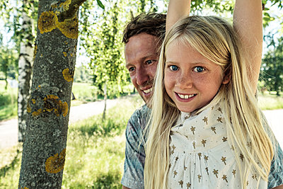 Portrait of a smiling girl with father hanging on a branch of a birch tree - p300m2160738 by Wilfried Feder