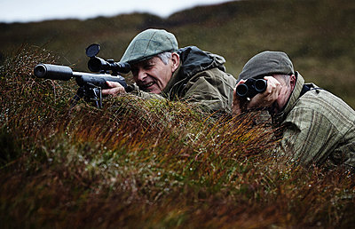 Man and gamekeeper deer stalking on moorland, Scottish Highlands - p429m2078988 by Patrick Williamson Photography