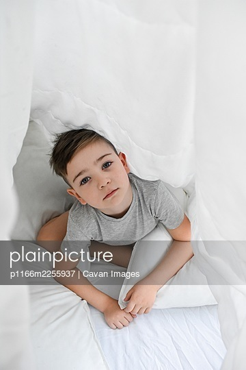 the boy hides under the blanket with a serious look on his face - p1166m2255937 by Cavan Images