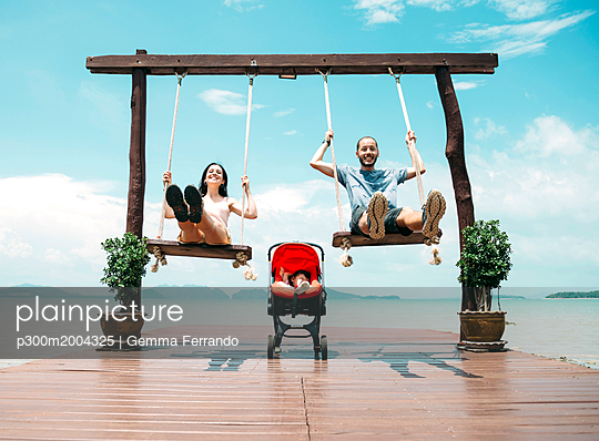 Thailand, Koh Lanta, happy parents  on wooden swings in front of the sea and sleeping baby in a stroller - p300m2004325 von Gemma Ferrando
