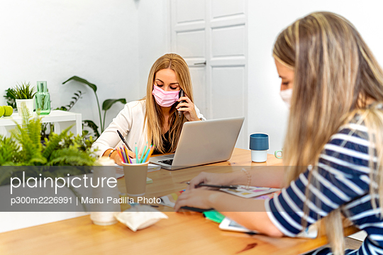 Blond woman talking on mobile phone while working with coworker at office - p300m2226991 by Manu Padilla Photo