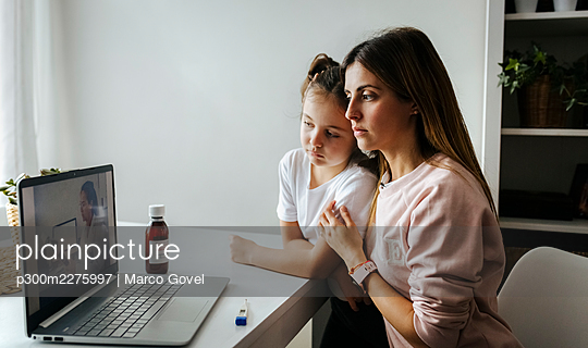 Mother and daughter listening to pediatrician over video call on laptop at home - p300m2275997 by Marco Govel