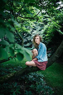 Junge Frau sitzt auf einem Baumstamm - p1046m1220970 von Moritz Küstner