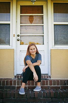 Lächelndes Mädchen vor ihrer Haustür - p1694m2291686 von Oksana Wagner