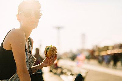 USA, New York, Coney Island, young woman eating a hamburger - p300m1113418f by Giorgio Fochesato
