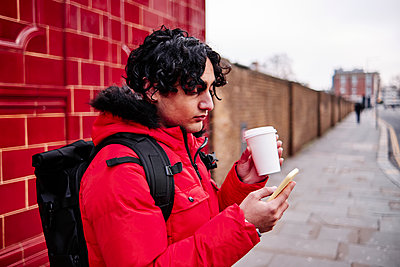 Young man using mobile phone while having coffee on footpath - p300m2264788 by Angel Santana Garcia