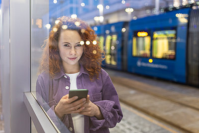Beautiful woman holding mobile phone looking through glass at tram station - p300m2293906 by William Perugini