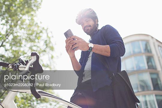 Man using smart phone on bicycle below sunny building - p1023m2208382 by Paul Bradbury