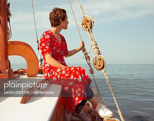 Frau sitzt entspannt auf einem Fischerboot - p432m2026108 von mia takahara