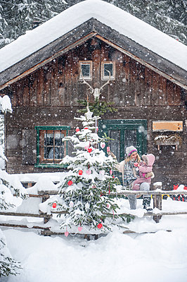 Austria, Altenmarkt-Zauchensee, mother with little son decorating Christmas tree at wooden house - p300m2041983 by Hans Huber