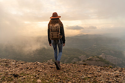 Woman with backback, standing on mountain, looking at view - p300m2079024 von VITTA GALLERY