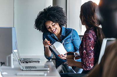 Smiling businesswoman having snack at desk - p300m2275655 by Josep Suria