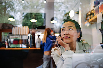 Mid adult woman with laptop contemplating while sitting in cafe - p300m2287268 by Angel Santana Garcia