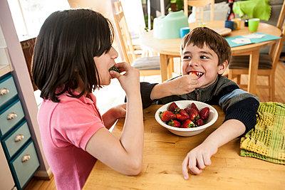 Hispanic children eating strawberries - p555m1454148 by Jon Feingersh