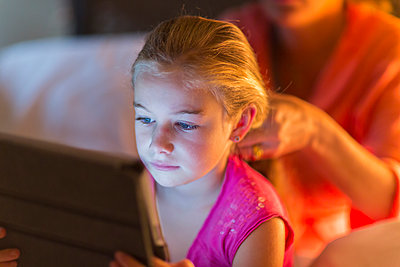 Caucasian girl using digital tablet as mother braids hair - p555m1463838 by Marc Romanelli