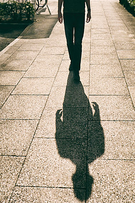 Man and his shadow walking towards camera - p597m1574521 by Tim Robinson