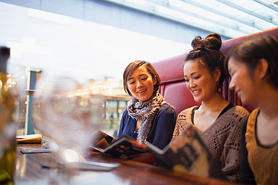 Young women reading menus in cafe - p924m836655f by NT Photography