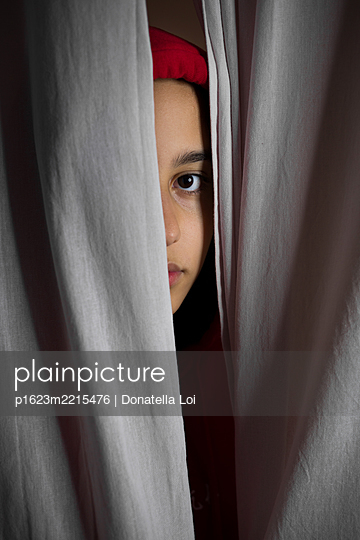 Girl portrait behind the curtain - p1623m2215476 by Donatella Loi
