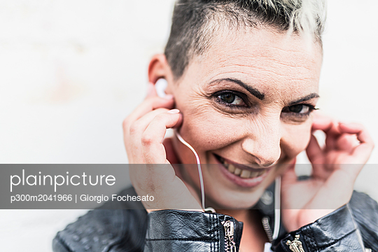 Portrait of smiling punk woman listening to music with earbuds - p300m2041966 von Giorgio Fochesato