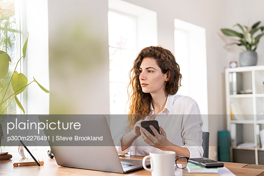 Beautiful female professional looking away while holding mobile phone at desk - p300m2276491 by Steve Brookland