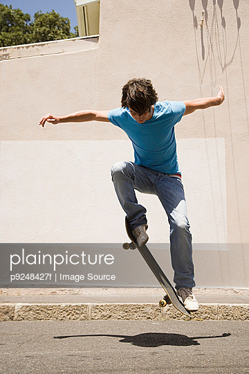 A teenage boy doing jumps with a skateboard - p9248427f by Image Source