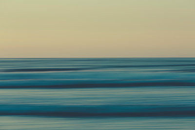 Ocean waves and the view to the horizon over the sea at dusk from the beach.  - p1100m1216311 by Mint Images