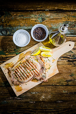 Roasted beefsteak with rosemary, and lemon on chopping board, salt, pepper and olive oil - p300m1536180 by Giorgio Fochesato