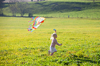 Little girl running in field with kite - p300m2103368 von Anette Christina Götz