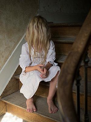 Girl in white dress sitting on steps - p945m1465920 by aurelia frey