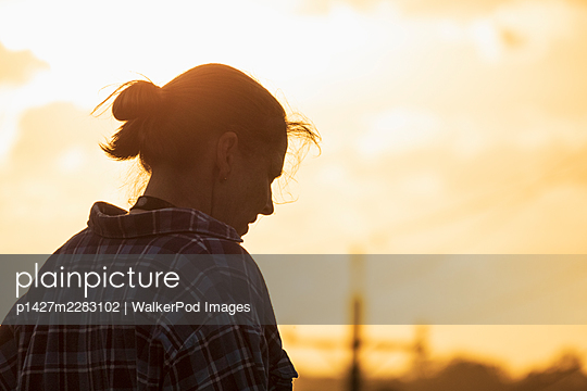 Silhouette of woman against sunset sky - p1427m2283102 by WalkerPod Images