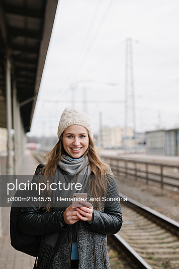 Portrait of smiling young woman with backpack and smartphone standing on platform - p300m2154575 von Hernandez and Sorokina
